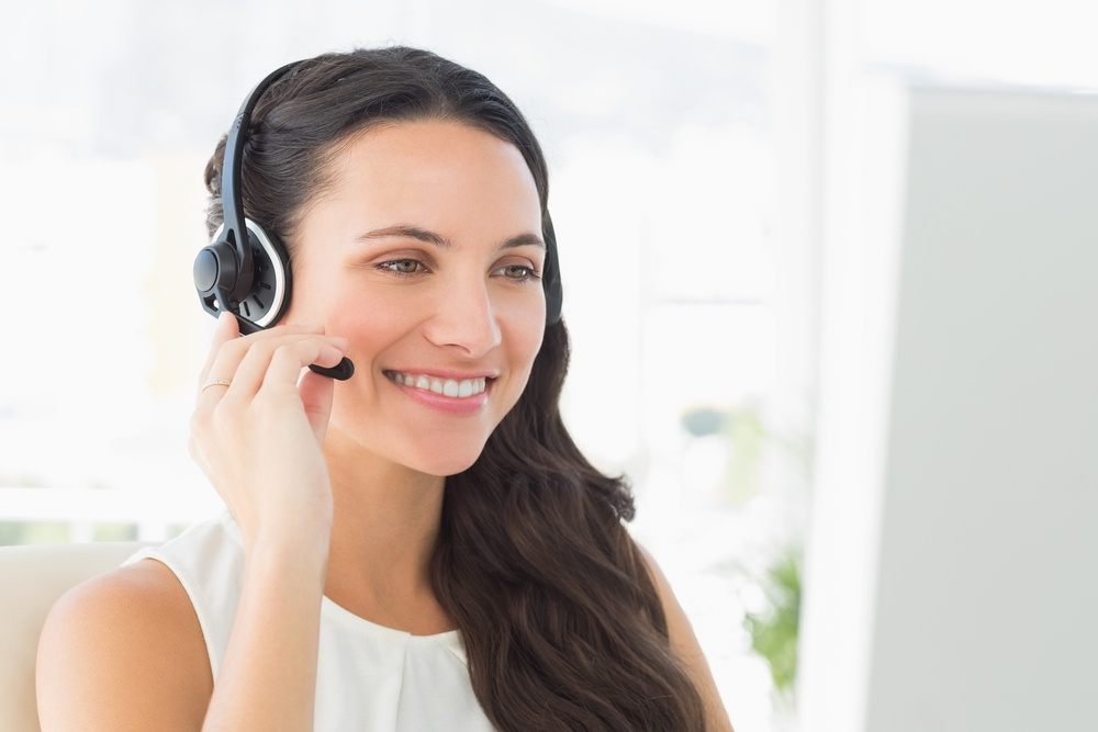 Cheerful call centre agent sitting at her desk in creative office.jpeg