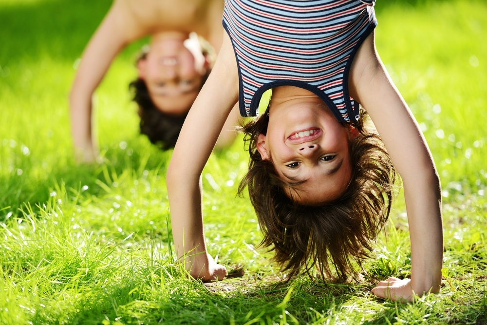 Portraits of happy kids playing upside down outdoors in summer park.jpeg