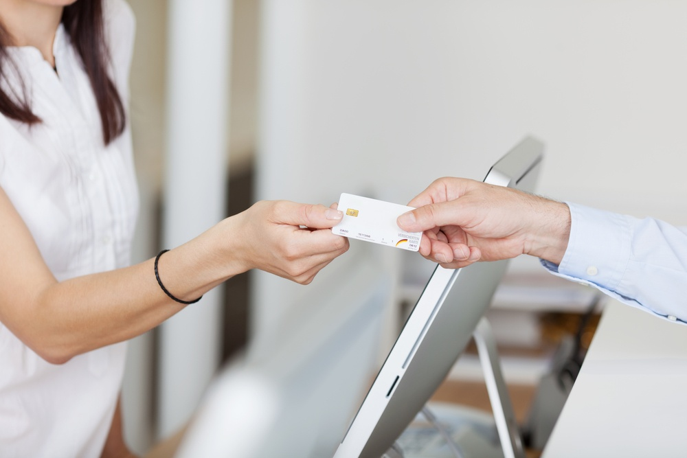 Closeup of receptionist receiving card from male patient in dentist clinic.jpeg