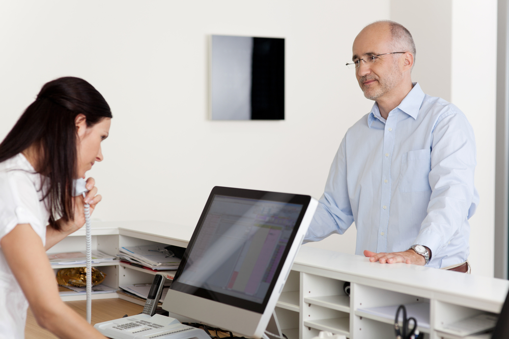 Mature male patient looking at female receptionist using landline phone and computer at reception in dentists clinic