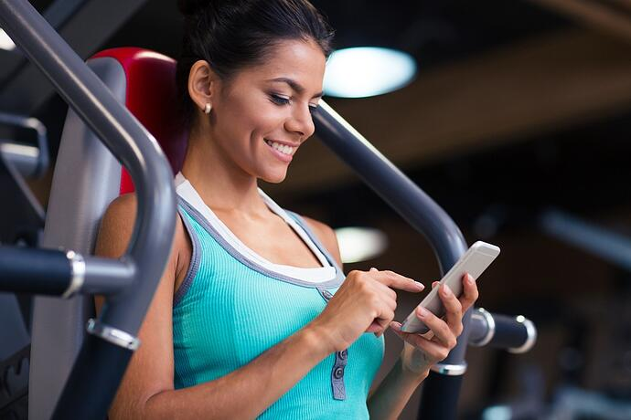 Portrait of a cheerful sports woman using smartphone in fitness gym.jpeg