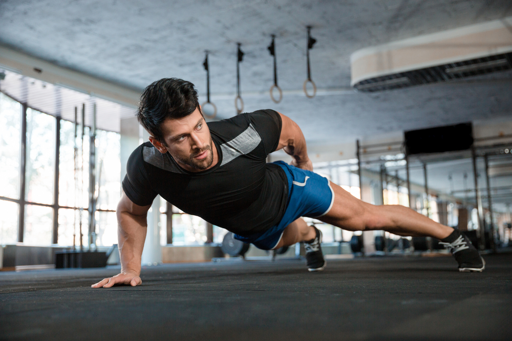 Portrait of a handsome man doing push ups exercise with one hand in fitness gym-1