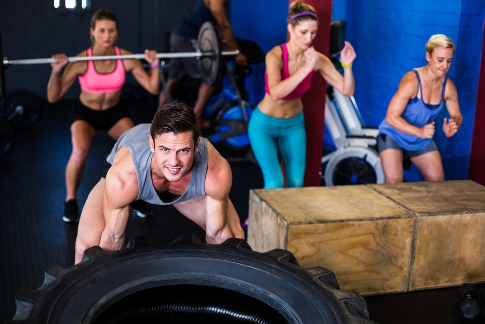 Portrait of smiling man lifting tire while exercising in gym