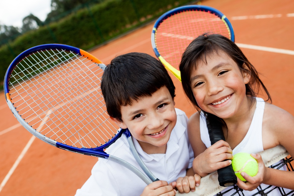 Portrait of young tennis players smiling at the court.jpeg