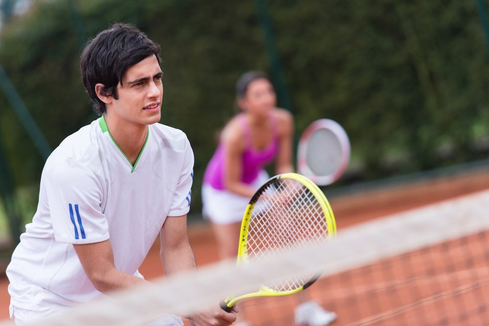 Tennis players at the court playing a doubles match.jpeg
