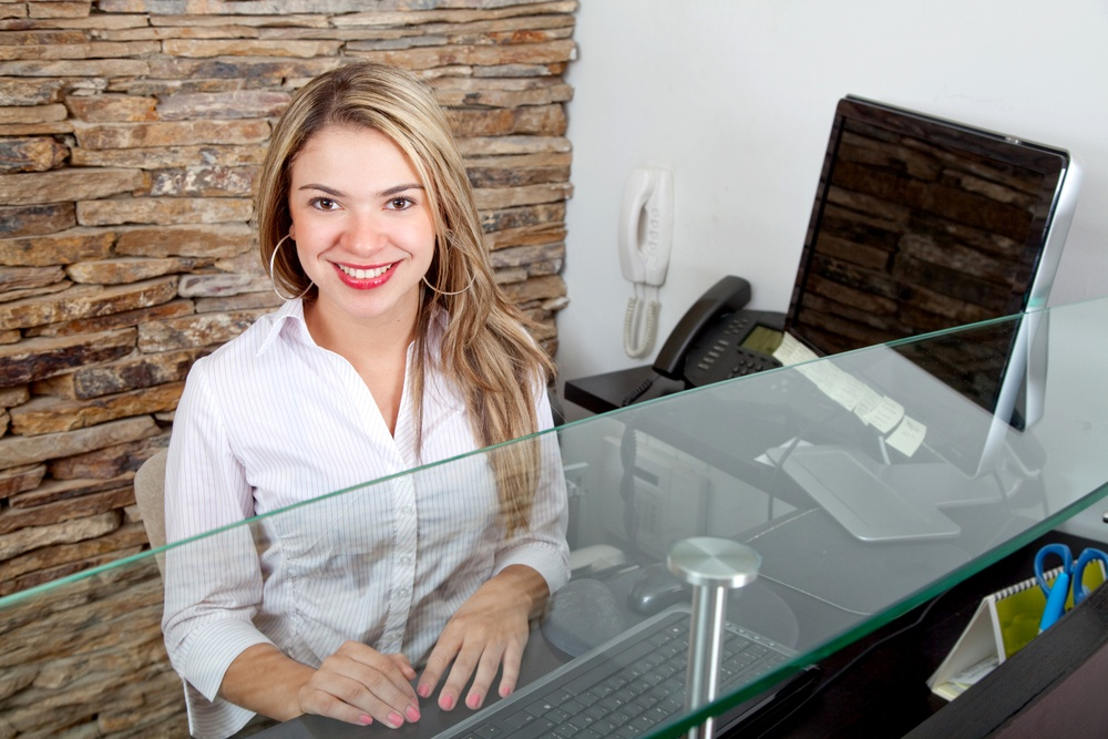 beautiful female receptionist smiling at the office.jpeg