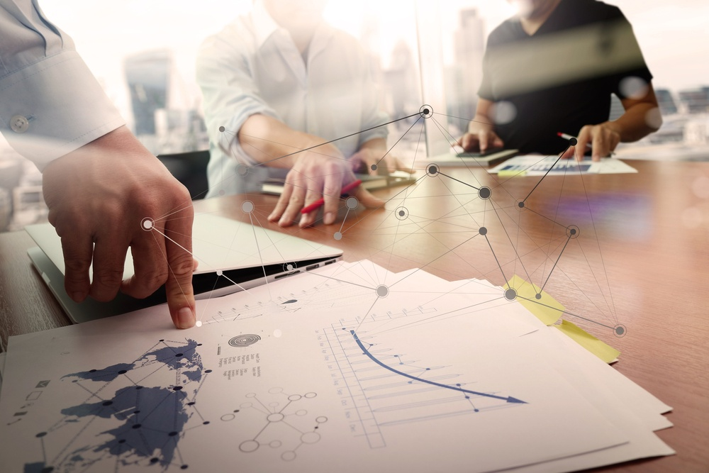 business documents on office table with smart phone and laptop computer and graph financial with social network diagram and two colleagues discussing data in the background.jpeg