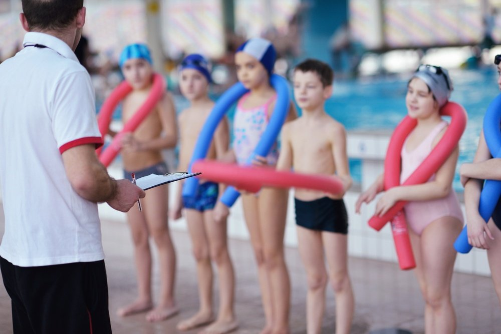 happy children kids group  at swimming pool class  learning to swim.jpeg